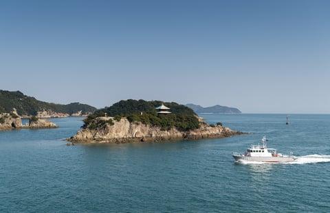 写真の主題である島と副題の船