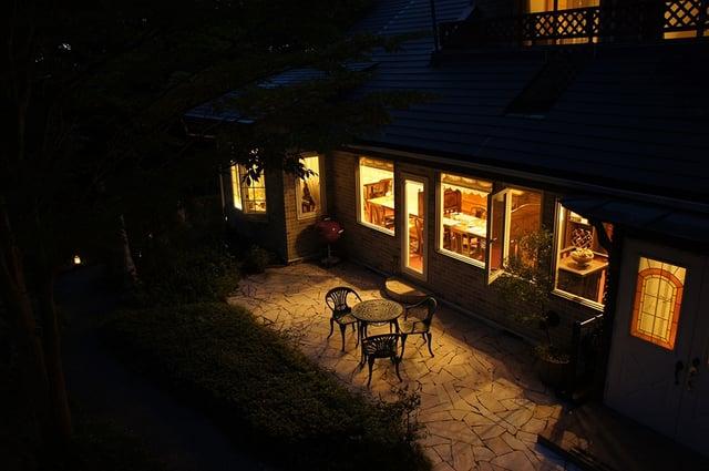 日暮れの後、室内の明かりが漏れる建物の外観写真
