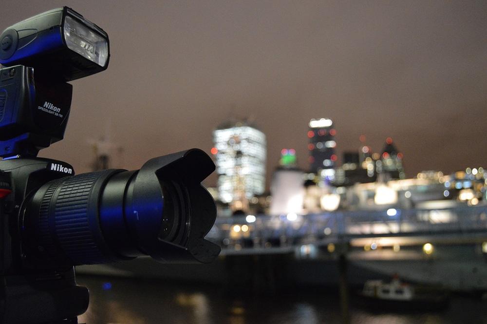 ビルなどの建物が並ぶ夜景を撮影するカメラの写真