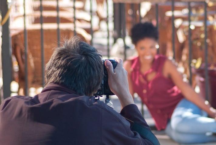 笑顔の女性モデルを撮影するカメラマン