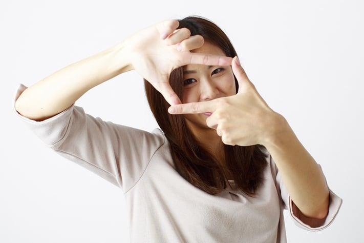 手でフレームを作って、被写体を切り取る女性