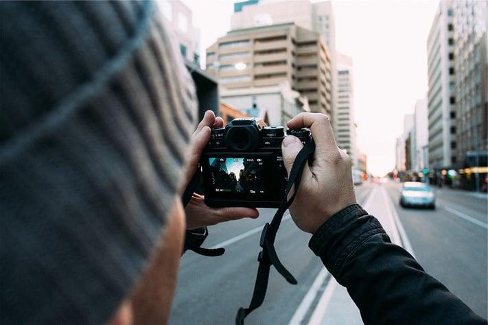 ビルの外観をカメラで撮影する男性
