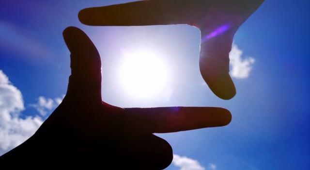 指で太陽をフレーミングしている写真